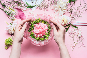 Pink Florist workspace with Lilies and other flowers, glass vase with water. Female hands making  Festive Flowers arrangements , top view