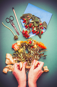 Female hand making autumn flowers arrangements on table workspace with scissors , envelope and ribbon, top view