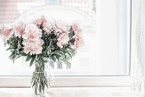 Beautiful pastel pink bouquet of peonies in glass vase on windowsill. Flowers in interior design. Cozy home.
