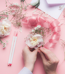 Female hands making floral arrangements with white flowers and ribbon at pastel pink background, top view