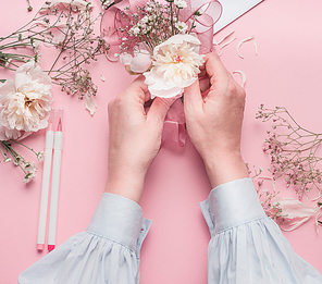 Female hands making floral arrangements with white flowers  at pastel pink background, top view