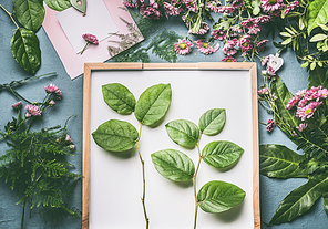 Creative florist workspace with flowers , greeting card mock up and beautiful  green leaves for arrangement , top view, flat lay