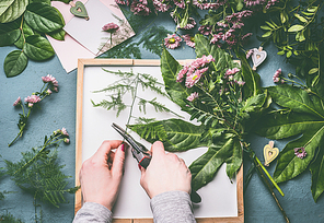 Female florist hands with scissors making floral arrangements flowers and green leaves on white tray , top view