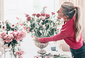 Florist women in red shirt, make beautiful big festive event classical bouquet with roses and other flowers in urn vase on table at window, lifestyle