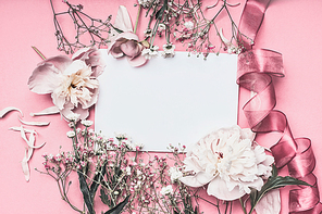 Flowers and petal arrangement around blank paper on pink background with ribbons, top view. Love feeling letter.  Instagram style. Wedding invitation. Mother's Day. Greeting concept. Flat lay