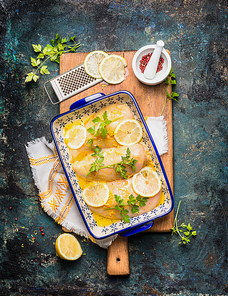 Lemon Chicken in baking dish with ingredients on wooden cutting board and rustic background, top view