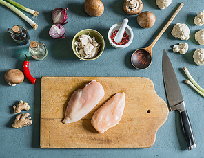 Two chicken breast on cutting board with knife on kitchen table background with ingredients , top view. Cooking preparation