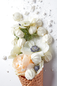 Sweet waffle cone with beautiful white peony flower and petals in a glass cup on a gray background with copy space. Summer concept of congratulations for Valentine's Day