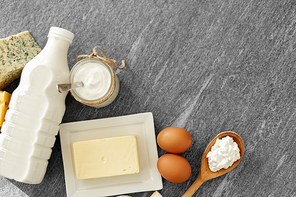 food and eating concept - different kinds of cheese, bottle of milk, yogurt and butter on stone table