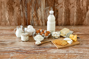 food and eating concept - close up of cottage cheese, crackers, bottle of milk, yogurt with butter and chicken eggs on wooden table