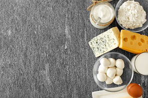 food and eating concept - close up of cottage cheese, bottle of milk, homemade yogurt with butter and chicken eggs on stone table