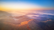 Aerial panorama of beautiful autumn mountains. Sunrise over mountain foggy valley. Misty woodland in the morning. Carpathians, Ukraine
