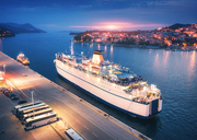 Aerial view of cruise ship in port at sunset. Landscape with ships and boats in harbour, city lights, buildings, mountains, blue sea at night. Top view. Luxury cruise. Floating liner at harbor at dusk