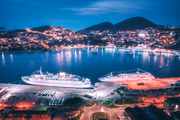 Aerial view of cruise ship in port at night. Landscape with ships and boats in harbour, city lights, buildings, mountains, blue sea at blue hour. Top view. Luxury cruise. Floating liner at harbor