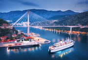 Aerial view of cruise ship at harbor and beautiful bridge at night. Landscape with ships and boats in harbour, city lights, road, mountain, blue sea at sunset. Top view. Floating liner in port at dusk