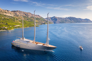 Luxury yacht and blue sea at sunset in summer. Aerial view of big modern sail boat. Top view of beautiful futuristic yacht, bay, boats, green trees, mountains, clear water, sky. Travel in Adriatic sea