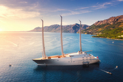 Luxury yacht and blue sea at colorful sunset in summer. Aerial view of big modern sail boat. Top view of beautiful futuristic yacht, lagoon, boats, mountains, clear water, sky. Travel in Adriatic sea