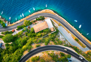 Aerial view of road, boats and yachts in water, buildings at sunset in spring. Colorful landscape with cars on roadway, sea coast, port, green trees in summer. Top view of highway in Croatia. Travel