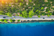 Aerial view of road in beautiful green forest and sea coast at sunset in spring. Colorful landscape with cars on roadway, blue water, trees in summer. Top view from drone of highway in Croatia. Travel