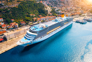 Aerial view of cruise ship in port at sunset in Dubrovnik, Croatia. Beautiful ships, boats and yachts. Landscape with harbor, city, mountains, blue sea. Luxury cruise. Top view of floating liner