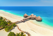 Aerial view of beautiful hotel on the water in ocean at sunset in summer. Zanzibar, Africa. Top view. Landscape with wooden hotel on blue sea, azure water, sandy beach, green palm trees. Luxury resort