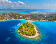 Aerial view of beutiful small island in sea bay at sunny day in summer in Murter, Croatia. Top view of transparent blue water, green trees, mountain, sandy beach, boats and yachts. Tropical landscape