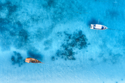 Aerial view of the fishing boat and yacht in clear blue sea at sunset in summer. Top view from drone of yachts, sandy beach. Travel in Zanzibar, Africa. Tropical landscape with motorboat, water