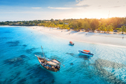 Aerial view of the fishing boats on tropical sea coast with sandy beach at sunset. Summer holiday in Zanzibar, Africa. Landscape with boat, yacht in transparent blue water, green palm trees. Top view