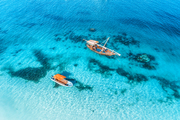 Aerial view of the fishing boats in transparent blue water at sunset in summer. Top view from drone of floating boat in Indian ocean in Zanzibar, Africa. Landscape with yachts in clear sea. Seascape