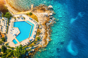 Aerial view of pool, sandy beach, stones, green trees, people and sea with transparent blue water at sunset. Top view of adriatic sea coast in summer. Landscape with azure water, rocks. Luxury resort