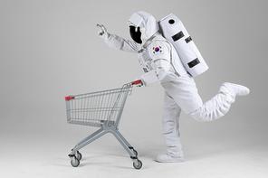 우주 생활 - 쇼핑카드 신나게 끌며 손가락으로 가리키는 우주인 옆모습 전신
