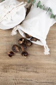 제로웨이스트 - 나무 배경, 식물과 흰 천 주머니에 들어있는 소프넛들 윗면