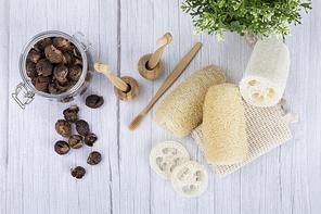 제로웨이스트 - 화분과 유리 병에 든 소프넛들, 대나무 칫솔 꽂이에 꽂혀진 대나무 칫솔, 천연 수세미들 윗면