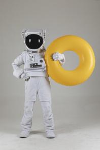 우주 생활 - 노란색 수영 튜브를 들고있는 우주인 전신