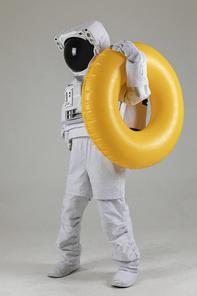 우주 생활 - 노란색 수영 튜브를 들고있는 우주인 옆모습 전신