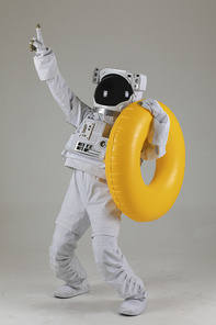 우주 생활 - 노란색 수영 튜브를 들고 손가락으로 가리키는 우주인 옆모습 전신