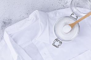 제로웨이스트 - 흰색 와이셔츠와 과탄산 소다가 들어있는 유리병과 나무 숟가락, 윗면