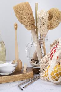 제로웨이스트 - 나무 도마 위에 있는 베이킹 소다가 든 유리 그릇과 대나무 칫솔과 칫솔 꽂이, 과일이 들어있는 네트백과 스텐 빨대들, 클로즈업