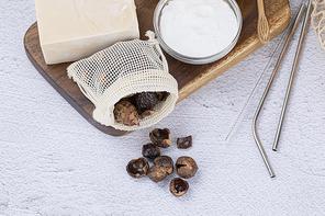제로웨이스트 - 나무 도마 위에 있는 소프넛이 들어있는 주머니와 천연 비누, 베이킹 소다가 들어있는 유리 그릇 과 스텐 빨대들, 클로즈업