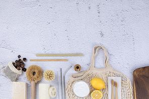 제로웨이스트 - 소프넛이 들어있는 주머니와 천연 비누, 대나무 빨대와 스텐 빨대들, 대나무 칫솔과 칫솔꽂이, 네트백과 레몬, 베이킹 소다가 들어있는 유리그릇, 천연 수세미와 청소 솔들, 나무 도마, 윗면 프레임
