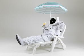 우주 생활 - 파라솔 아래, 선배드 위에 다리꼬고 누워서 칵테일 한 잔 마시며 휴식을 취하고 있는 휴가 중인 여유로운 우주인