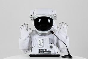 우주 생활 - 키보드와 마이크 앞에 앉아서 시청자들과 손인사를 하고 있는 우주인 앞모습 상반신