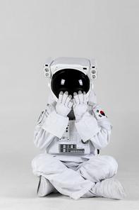 우주 생활 - 바닥에 앉아서 양 손으로 얼굴을 가리며 놀라고 있는 우주인 앞모습