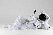 우주 생활 - 옆으로 누워서 스마트폰 화면을 보고 있는 우주인 앞모습