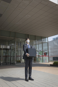 코로나 시대의 신입사원 - 퇴사 짐을 들고 멀리 바라보는 마스크 착용한 청년 신입사원