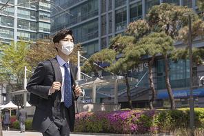 코로나 시대의 신입사원 - 가방을 쥐고 출근하는 마스크 착용한 청년 신입사원
