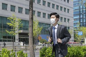 코로나 시대의 신입사원 - 가방을 쥐고 뛰어가며 출근하는 마스크 착용한 청년 신입사원