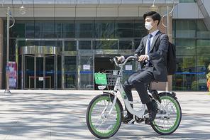 코로나 시대의 신입사원 - 공유 자전거를 타고 출근하는 마스크 착용한 청년 신입사원
