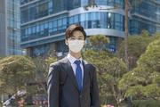 코로나 시대의 신입사원 - 빌딩 앞에 서서 눈웃음을 짓는 마스크 착용한 청년 신입사원