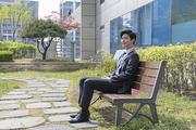 청년 신입사원의 하루 -  옥상 정원 벤치에 앉아 웃고 있는 활기찬 청년 신입사원